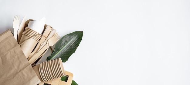 Papierowa torba z jednorazową ekologiczną zastawą stołową, talerzami, okularami tło widok z góry