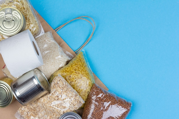 Papierowa torba z kryzysowym zaopatrzeniem w żywność na okres izolacji kwarantannowej koronawirusa, ryżu, makaronu, płatków owsianych, żywności w puszkach, papieru toaletowego, gryki na niebieskim tle