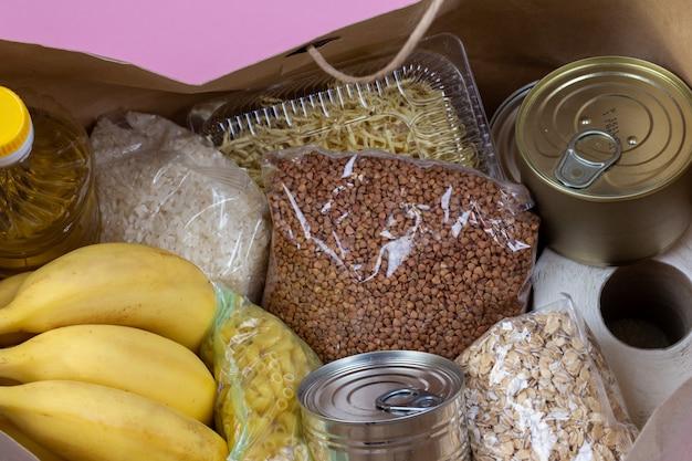 Papierowa torba z kryzysowym zaopatrzeniem w żywność na okres izolacji kwarantanny na różowym tle, makaron, gryka, konserwy, ryż, banany z bliska.