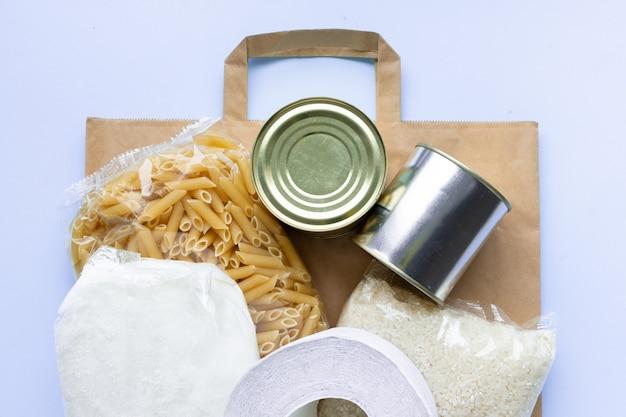 Papierowa torba z okresem izolacji zapasów żywnościowych kryzys na niebiesko. ryż, makaron, płatki owsiane, konserwy, cukier, papier toaletowy.