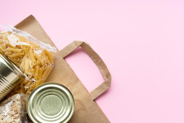 Papierowa torba z okresem kryzysu zapasów żywnościowych na różowo. ryż, makaron, płatki owsiane, konserwy, cukier, papier toaletowy. dostawa jedzenia,