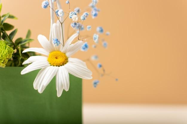 Papierowa torba z pięknymi letnimi kwiatami i roślinami na beżowym tle
