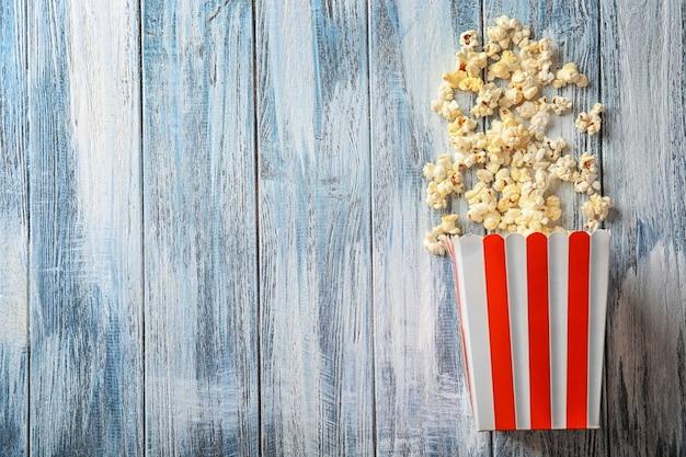 Papierowa torba z popcornem na drewnianym stole