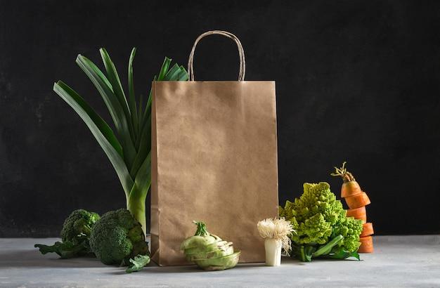 Papierowa torba z różną zdrową żywnością na ciemnym tle. zakupy supermarket spożywczy i koncepcja planu żywienia