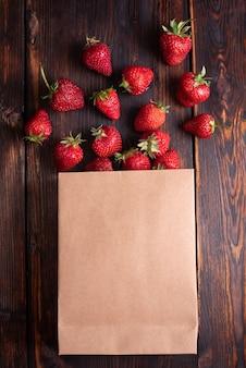Papierowa torba ze świeżymi truskawkami na drewnianym tle, letnie jagody wylewające się z torby, z bliska.