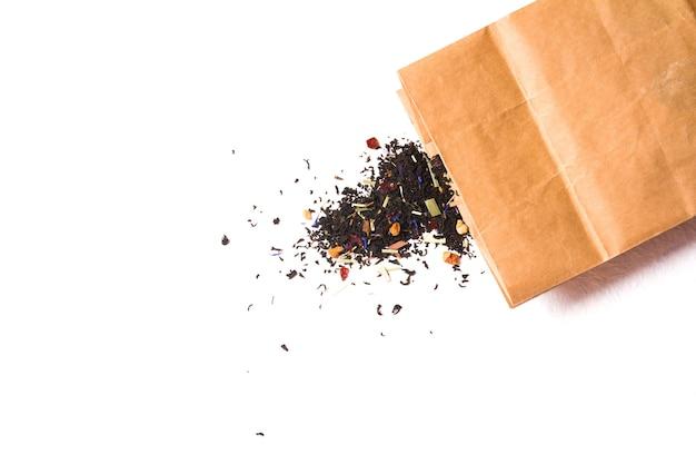 Papierowa torebka z suchą luźną herbatą liściastą, herbatą z dodatkiem owoców, jagód i ziół leczniczych na białej powierzchni
