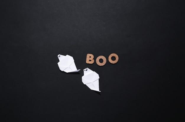 Papierowe duchy i słowo boo na czarnym tle. motyw halloween