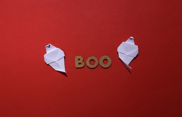 Papierowe duchy i słowo boo na czerwonym tle. motyw halloween