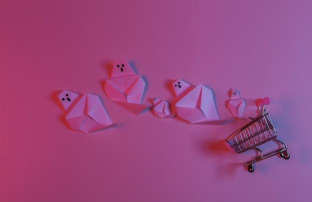 Papierowe duchy origami i wózek na zakupy w czerwono-niebieskim neonowym świetle. motyw halloween
