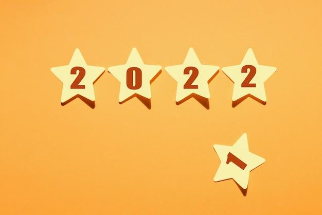 Papierowe gwiazdki z 2022 roku i odrzucona gwiazda z numerem 1 na żółtym tle, życzenia noworoczne.
