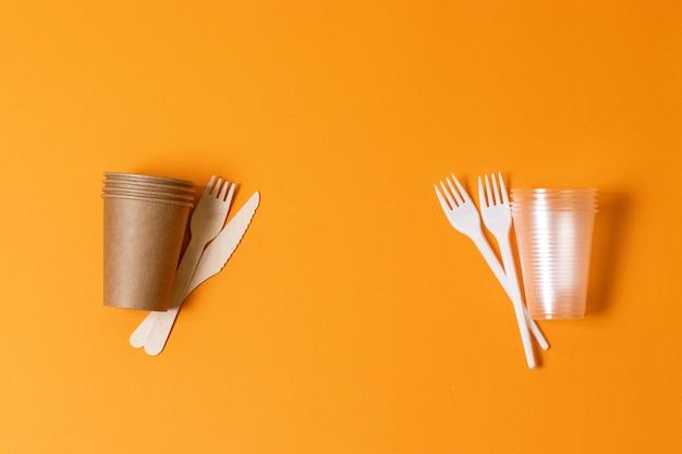 Papierowe i plastikowe naczynia na pomarańczowym tle. koncepcja konfrontacji. ochrona przyrody. problemy ekologii, recyklingu i zbawienia przyrody.