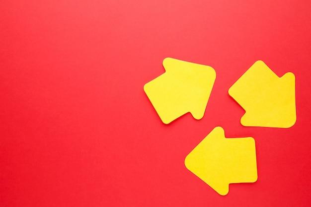 Papierowe karteczki w kształcie strzały na czerwonym tle