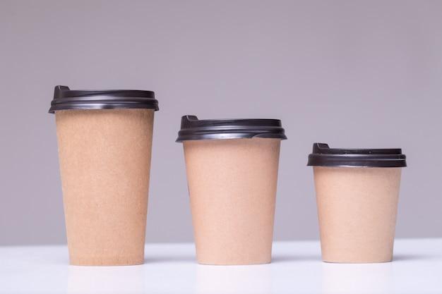 Papierowe kubki do kawy o różnych rozmiarach na szarym tle
