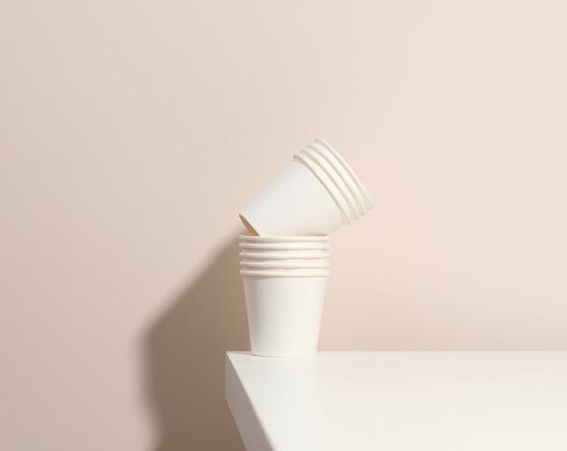 Papierowe kubki kartonowe białe do kawy, beżowe tło. ekologiczna zastawa stołowa, zero odpadów
