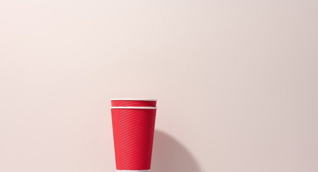 Papierowe kubki kartonowe czerwone do kawy, beżowe tło. ekologiczna zastawa stołowa, zero odpadów