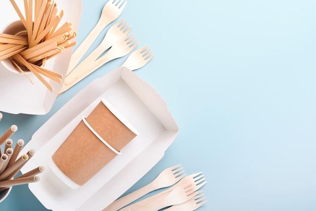 Papierowe kubki, naczynia, torebki, drewniane widelce, słomki do picia, pojemniki na fast food, drewniane sztućce na jasnoniebieskim tle. zastawa stołowa z ekologicznego papieru rzemieślniczego. koncepcja recyklingu i dostawy żywności. makieta. widok z góry