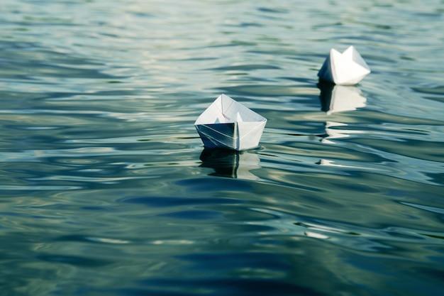 Papierowe łódki wykonane z kartki szkolnego zeszytu unoszącego się w wodzie