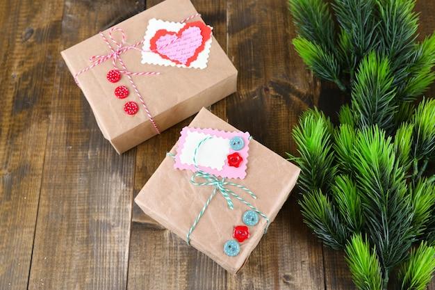 Papierowe pudełka na prezenty na drewnianym tle