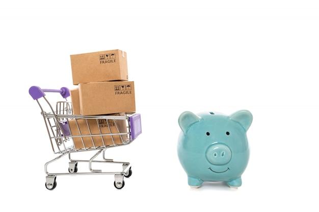 Papierowe pudełka w wózku z piggy bank na białym background.concept oszczędności zakupy online