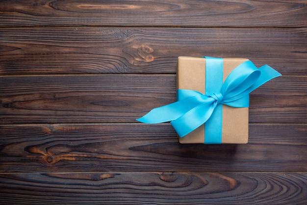 Papierowe pudełko z niebieską wstążką na ciemnym drewnianym świąteczny prezent, widok z góry z miejsca kopiowania