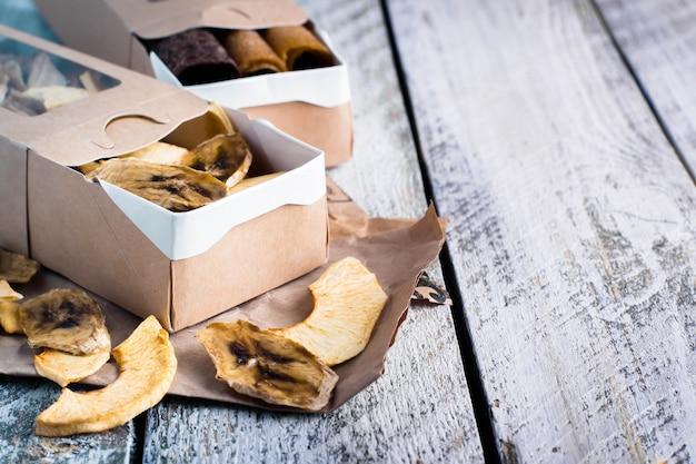 Papierowe pudełko z owocowymi jabłkami i bananowymi układami scalonymi na drewnianym stołowym tle.