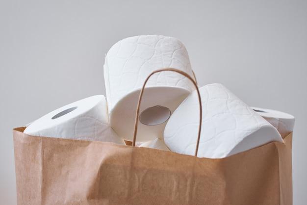 Papierowe rolki toiket w torbie na zakupy. kupowanie paniki na temat koronawirusa covid-19 do kwarantanny domowej