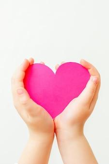 Papierowe różowe serce w rękach dziecka