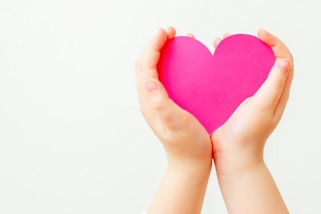 Papierowe różowe serce w rękach dziecka.