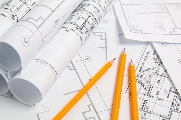 Papierowe rysunki architektoniczne, plan i ołówek. projekt techniczny