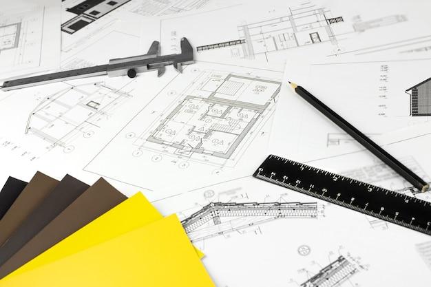 Papierowe rysunki architektoniczne. tło budowlane. narzędzia inżynierskie.