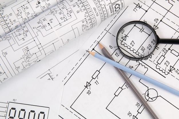 Papierowe rysunki elektrotechniczne, ołówek i szkło powiększające