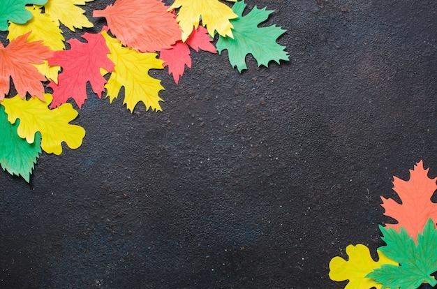 Papierowe rzemiosło, czerwone i żółte jesienne liście. widok z góry na mieszkanie leżał na ciemnym tle betonu.