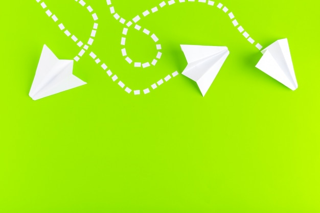 Papierowe samoloty połączone kropkowanymi liniami na zielonym tle. pomysł na biznes