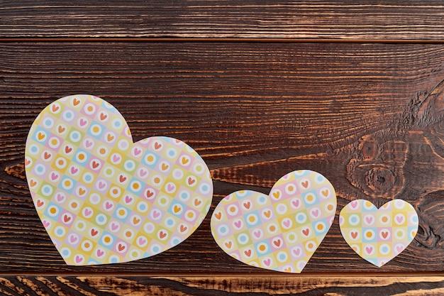 Papierowe serca na brązowym tle drewnianych. wiersz serc papieru na baner z miejsca na kopię na górze.