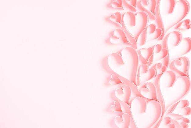Papierowe serca na różowym papierze pastelowym