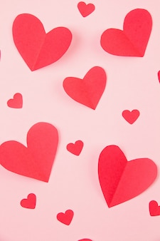 Papierowe serca na różowym pastelowym tle