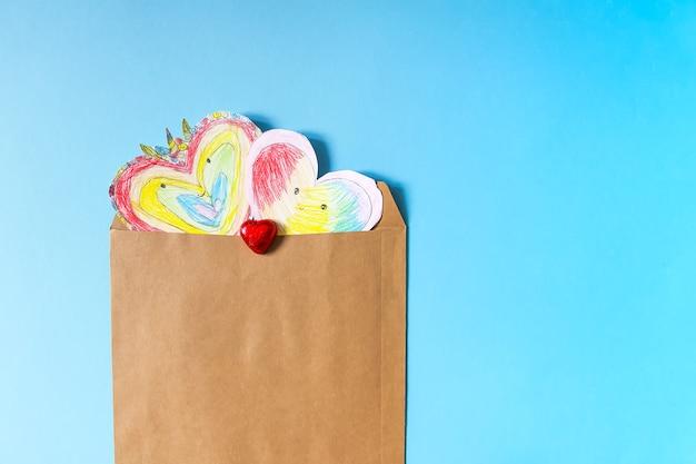 Papierowe serca w papierowej kopercie rzemieślniczej na niebieskim tle. dziecka kreacja na walentynki.