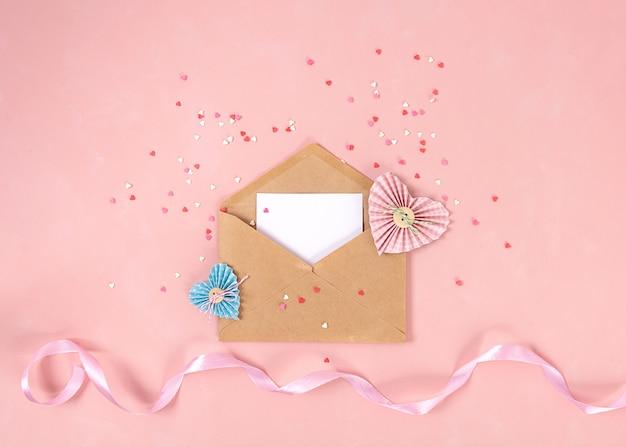 Papierowe serca w technice scrapbookingu oraz różowe i czerwone słodycze cukrowe serca wylatują z papierowej koperty.