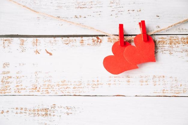 Papierowe serca z pinami zaczepiającymi o nitkę