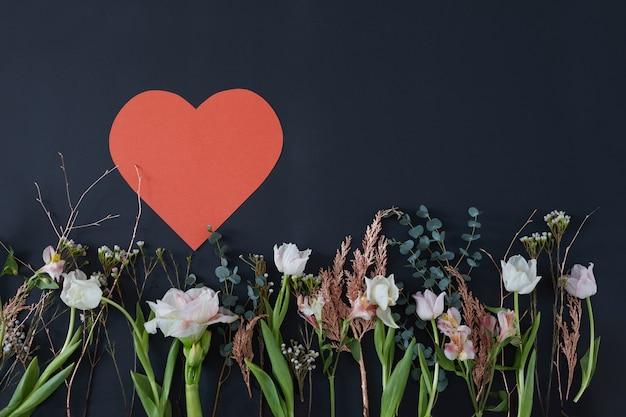 Papierowe serce na ciemnym tle w otoczeniu kwiatów