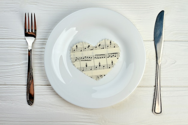 Papierowe serce z nutami na białym talerzu. nakrycie stołu z talerzem, widelcem i nożem. koncepcja muzyki i miłości.