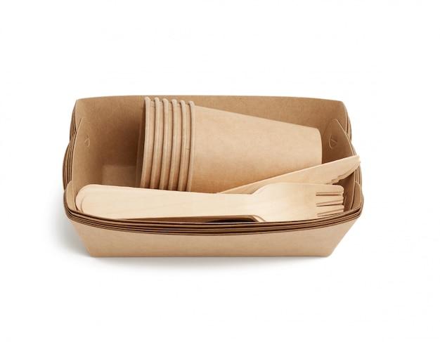 Papierowe talerze i kubki z brązowego papieru rzemieślniczego oraz drewniane widelce i noże