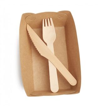 Papierowe talerze z brązowego papieru rzemieślniczego oraz drewniane widelce i noże