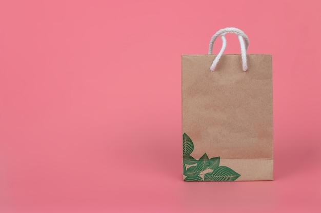 Papierowe torby na pastelowych różowych tło, pojęcie ochrony środowiska.