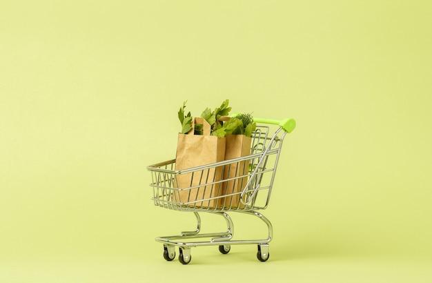 Papierowe torby na zakupy ze świeżą zieloną sałatą w koszyku, wózku.