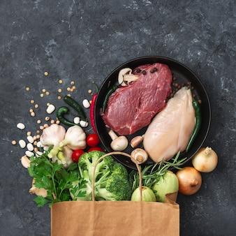 Papierowe torby żywności z warzywami, owocami i mięsem na ciemności