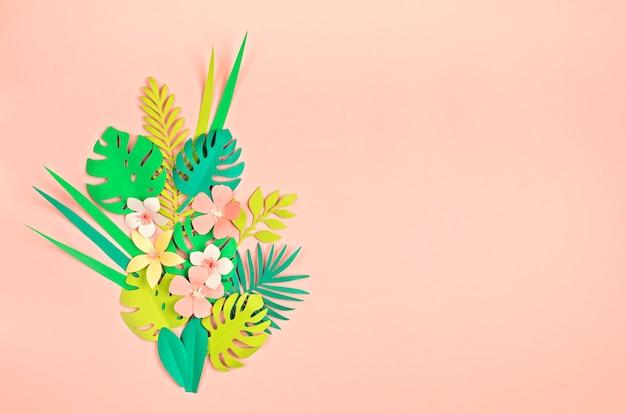 Papierowe tropikalne liście i kwiaty na różowej pastelowej ścianie. letnie egzotyczne wakacje, płaski widok z góry