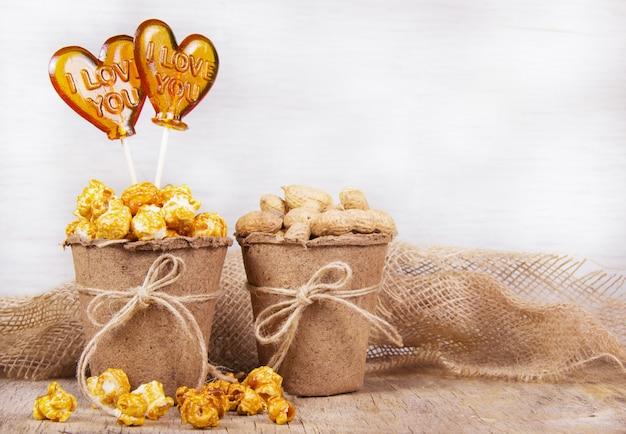 Papierowe wiadro karmelowego popcornu, orzeszków ziemnych i lizaka
