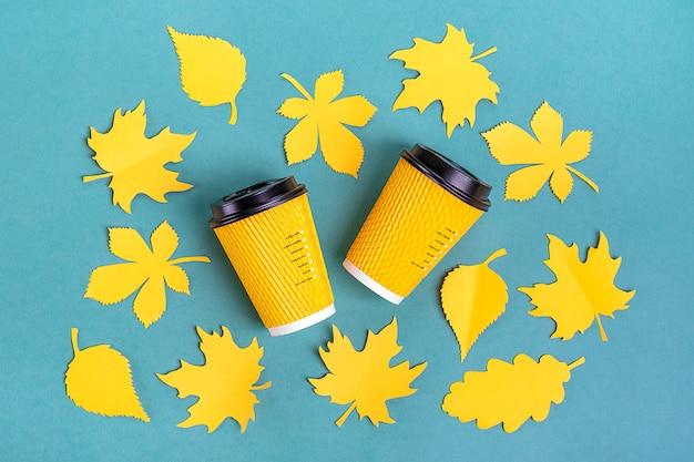 Papierowe żółte filiżanki kawy i jesienne liście wycięte z papieru na niebiesko