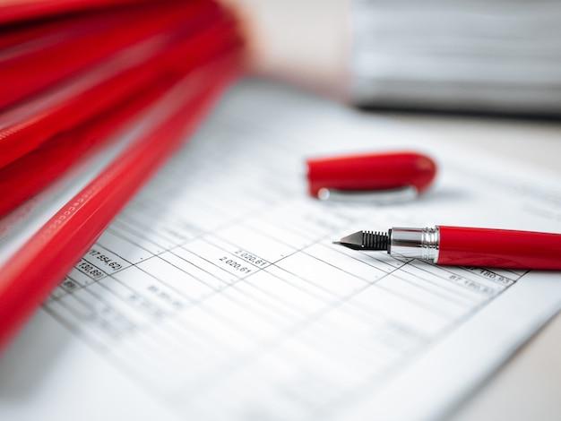 Papierowego raportu czerwonego pióra miejsca pracy biuro
